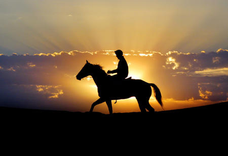 Jockey Todd Austin does trackwork at sunrise on the day of the Australian outback horse races at Birdsdville, about 1,400 km (870 miles) west of Brisbane, on September 7, 2002. The colourful annual races, which are run in the sand, attract thousands of people travelling hundreds of kilometres across the Simpson Desert to the outback town of Birdsville. REUTERS/Peter Wallis